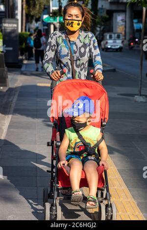 Fille portant un masque de visage poussant la chaise de poussée avec bébé pendant la pandémie de Covid 19, Bangkok, Thaïlande