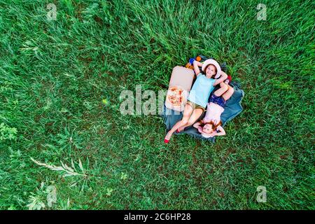 deux petites filles ont un pique-nique avec pizza et sont allongées sur une herbe verte, vue aérienne du dessus Banque D'Images