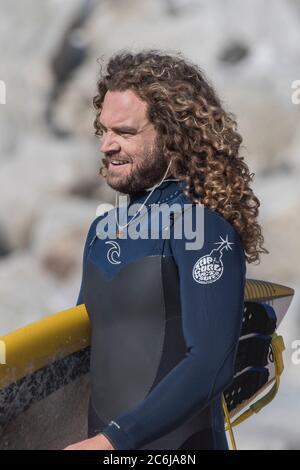 Un surfeur mâle aux cheveux longs et bouclés portant sa planche de surf à Fistral à Newquay en Cornouailles. Banque D'Images
