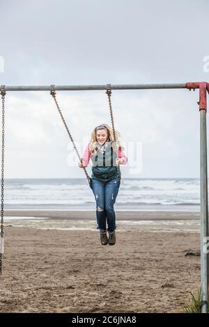 Une femme d'âge moyen se balançant sur une balançoire sur Seaside Beach, Oregon, États-Unis.