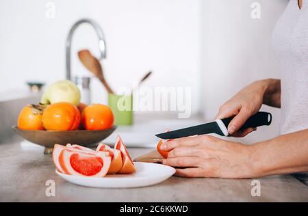 Les mains de la jeune femme hachent du pamplemousse à l'aide d'un couteau et d'une planche à découper dans une cuisine moderne. Beaucoup de pommes, de pamplemousse, de kaki et d'oran