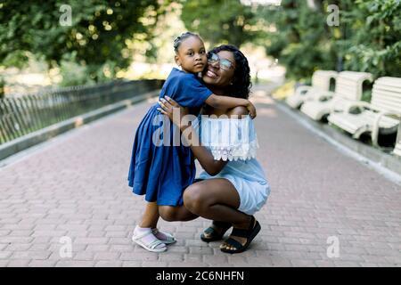 Portrait en longueur de jeune fille africaine souriante embrassant sa petite fille avec tendresse et amour debout dans le parc. Mère et