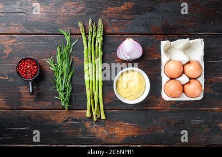 Œufs d'asperges frais et ingrédients de la vinaigrette française avec moutarde de dijon, estragon d'oignon sur fond de bois sombre, vue du dessus.