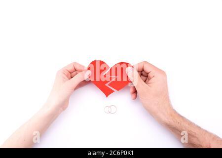 Les mains de sexe féminin et masculin tiennent un cœur brisé sur un fond blanc avec des anneaux de mariage. Problèmes de mariage, divorce Banque D'Images