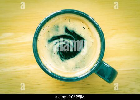 Café expresso et crème dans une tasse sur table en bois avec lumière naturelle dans un ton vintage