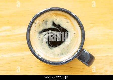 Café expresso et crème dans une tasse sur table en bois avec lumière naturelle