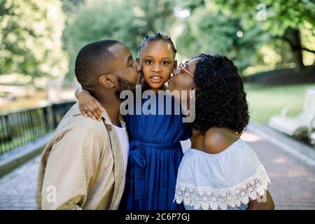 Adorable portrait d'été de la jeune famille africaine de trois personnes qui se posent ensemble à l'extérieur dans un beau parc. Les parents adorables embrassaient leur petite fille