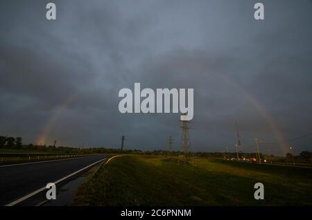 Rainbow sur la ligne électrique. Câbles et piliers sous la pluie