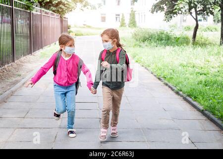 Deux filles qui reviennent à l'école pendant une pandémie de coronavirus. Élèves de l'école primaire avec des sacs d'école portant un masque facial de protection allant à l'école.