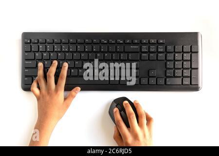 Clavier et souris sans fil noirs isolés sur fond blanc. Peron nouant et maintenant la souris en main.
