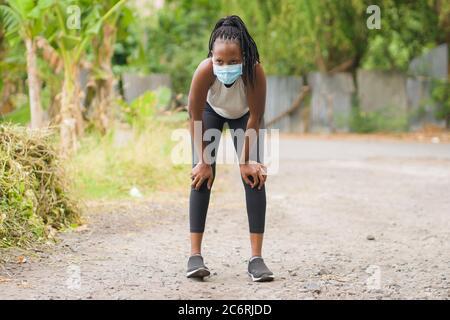 Coureur fille style de vie pendant la post-quarantaine nouvelles heures normales - jeune attrayant et en forme noir afro femme américaine respiration fatiguée et épuisée après
