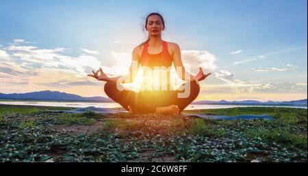 Les femmes asiatiques s'exercent avec le yoga à l'extérieur près de la rivière dans la soirée Banque D'Images