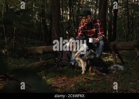 Backpacker Tourist avec Aussie Australian Breed Dog Taling a Rest Afther roulant dans la forêt. Style de vie actif avec les animaux Banque D'Images