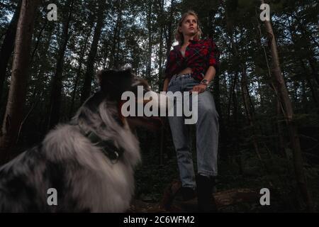 Chien australien avec une belle femme routard se promenant et randonner dans la forêt. Style de vie actif avec les animaux Banque D'Images