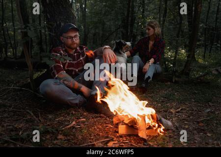 Belle Backpacker femme et homme ayant le repos près de Bonfire après Promenade et randonnée dans la forêt avec chien australien Banque D'Images
