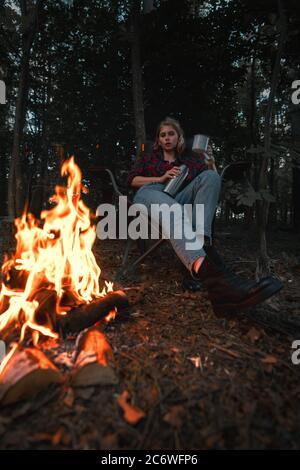 Belle femme de randonnée ayant le repos près de Bonfire après se promener et Randonnée dans la forêt et thé versant dans un mug métallique de Thermos