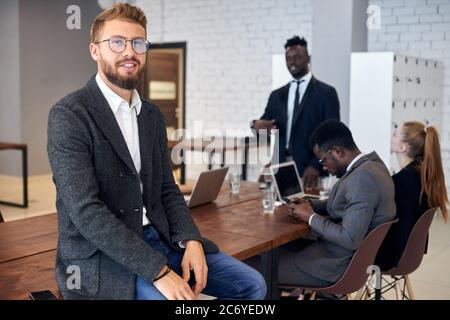 Un homme attrayant qui regarde la caméra en toute confiance pendant que ses partenaires commerciaux ont des discussions au bureau