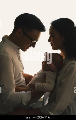 Joyeux jeune père, mère et mignon petit garçon sur blanc. Silhouette sombre, profil. Banque D'Images