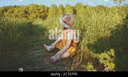 Enfant assis sur l'herbe bébé fille jouant en plein air famille vacances d'été marcher dans la nature de forêt