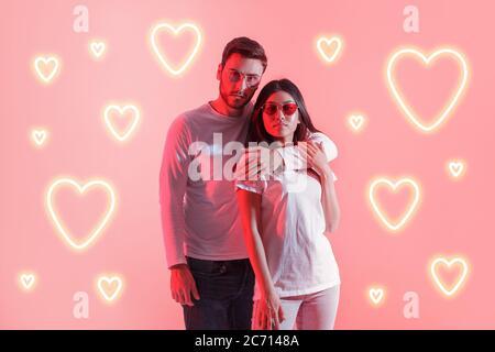 Amour et néon. Jeune homme et femme asiatique en lunettes avec cœur