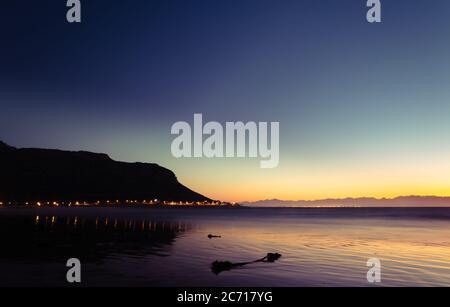 Vue sur le lever du soleil au-dessus de False Bay depuis Fish Hoek Beach avec des montagnes en arrière-plan, le Cap, Afrique du Sud Banque D'Images