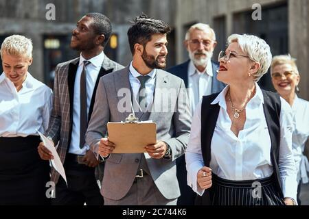 Groupe de gens d'affaires très occupés dans différents costumes en marchant dans la rue. Au premier plan, l'homme barbu de brunette regarde la blonde en chemise blanche. Dans le