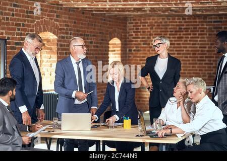 Groupe d'hommes d'affaires en costumes élégants à la table dans le bureau fait des murs de briques déplacer et discuter de projet. Ordinateurs portables blancs et noirs sur la table et des lunettes de wa Banque D'Images