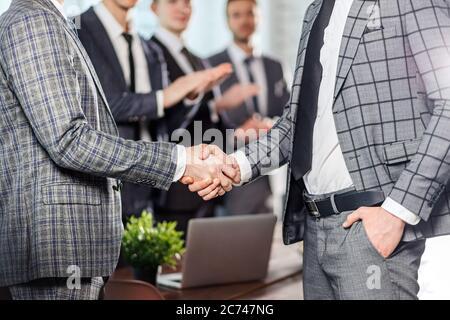 gros plan des gens d'affaires, des jeunes hommes qui se secouent la main, portant des tuxedo gris élégant, des collègues heureux d'hommes applaudisse à eux en arrière-plan