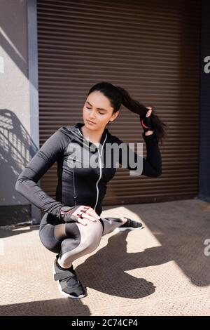 foyer sélectif de la belle jeune sportswoman s'étendant à l'extérieur tout en touchant les cheveux Banque D'Images