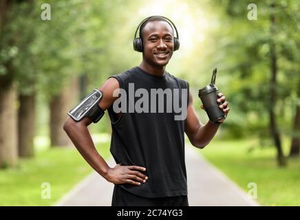Jeune homme noir boit de l'eau pendant son entraînement au parc