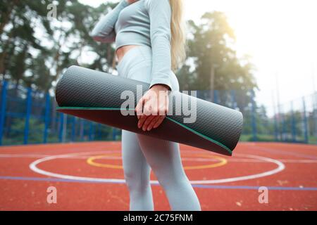 Concept de forme physique, de sport et de mode de vie sain. Image courte de jeune fille en vêtements de sport gris, tenant un tapis d'exercice et marchant à l'extérieur du sport