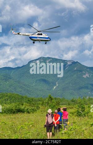 Groupe de femmes voyageurs regardant le vol de l'hélicoptère touristique russe mi-8 dans le ciel sur fond de montagnes, forêt verte Banque D'Images