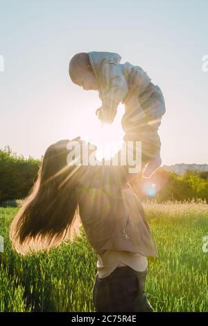 Une fille heureuse tient son enfant dans ses bras et le jette un jour ensoleillé au coucher du soleil Banque D'Images