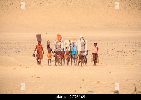 Femme Himba et les enfants travaillant au transport de l'eau pour un village de tribu Himba peuple autochtone de la région de Kunene, le nord de la Namibie, l'Afrique du Sud-Ouest