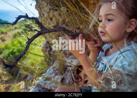 Portrait d'un petit garçon mignon jouant dans la forêt avec Magic Stick. Imagination d'un petit enfant. Enfant jouant son propre jeu. Bonne enfance de Carefree