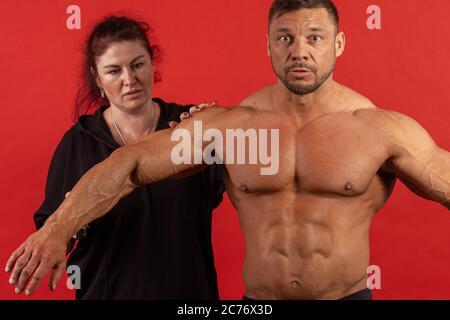 Un athlète masculin et une femme vêtue de noir, enduisez le corps d'huile avant la performance. Banque D'Images