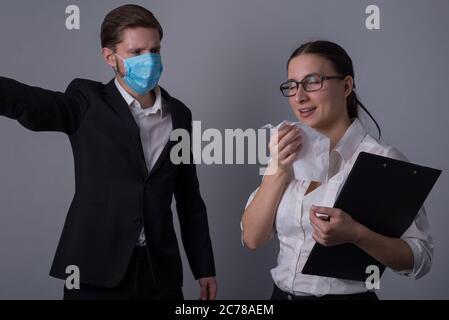 Portrait de deux jeunes hommes d'affaires en vêtements d'affaires. Le gars dans le masque montre sa main sur le côté, une fille malade qui éternue en mouchoir. Banque D'Images