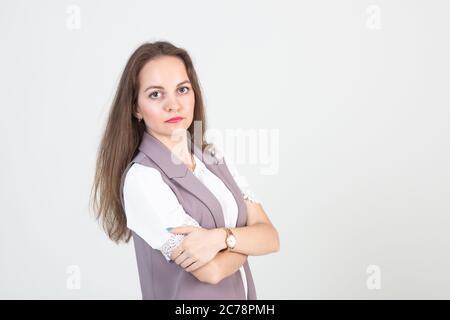 belle jeune femme en affaires vêtements stricts pose contre un mur blanc Banque D'Images
