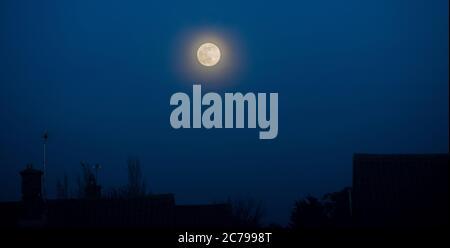 La lune s'élève avec la lune qui brille au-dessus des bâtiments domestiques et du ciel bleu foncé Banque D'Images