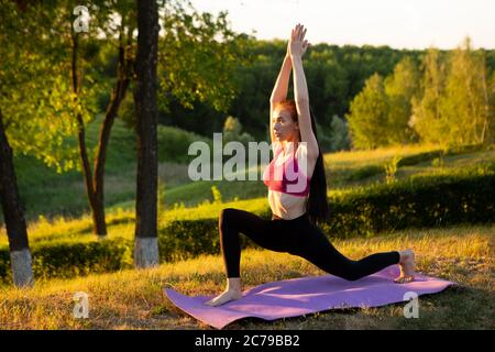 La fille fait des exercices le matin sur un fond de nature Banque D'Images