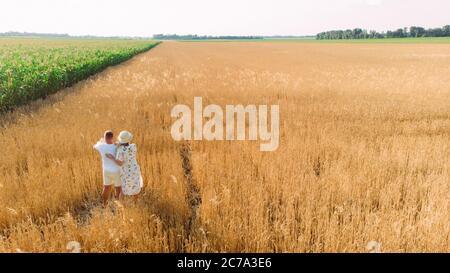 Une famille heureuse se promène dans un champ de blé jaune près du maïs avec bébé. Copier l'espace.