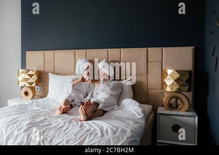 Un jeune couple d'hommes et de femmes en peignoirs blancs et serviettes sur la tête sont couchés dans le lit avec des verres de vin.