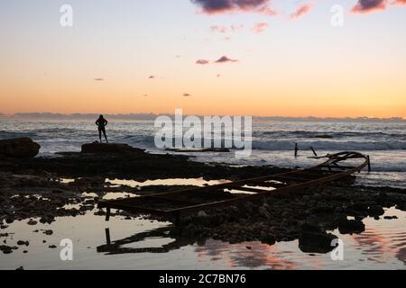 Silhouette de femme qui regarde loin de la mer Méditerranée, près d'un quai en métal abandonné sur une plage, au coucher du soleil, à Batroun, Liban, Middel est