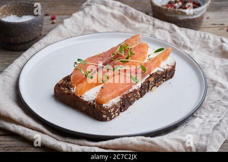 Pain de seigle au saumon fumé, fromage à la crème sur une ancienne table en bois. Smorrebrod