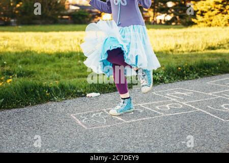 Gros plan de chld fille jouant saut de hopscotch en plein air. Jeu d'activités amusant pour les enfants sur l'aire de jeux à l'extérieur. Sports de rue de cour d'été pour les enfants.