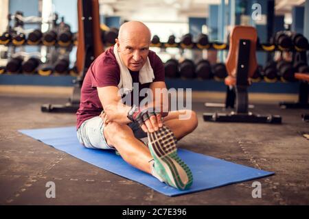 Un portrait d'homme âgé chauve qui s'étire après l'entraînement dans la salle de gym. Concept de personnes, de soins de santé et de mode de vie