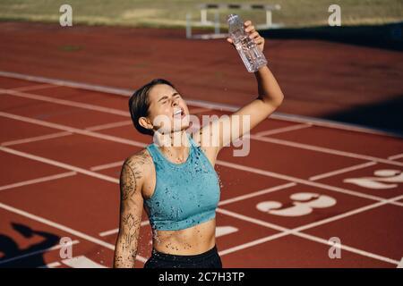Une athlète en herbe, une fille de sportswear qui se déverse de l'eau fraîche après avoir fait ses courses dans le stade Banque D'Images