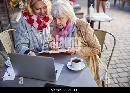 Deux belles femmes assises à la table avec un ordinateur portable à l'extérieur