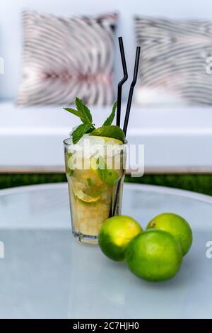 image d'un cocktail mojito fraîchement préparé sur une table avec garniture de citron vert