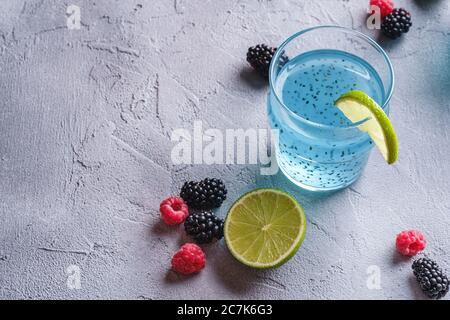 Délicieux cocktail de couleur bleue avec graines de basilic chia, tranche de citron vert, framboise et mûres de mûre en verre, boisson d'été saine